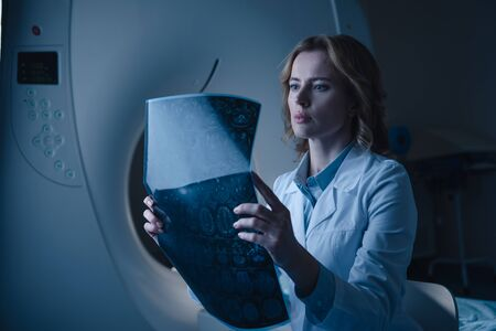 Beautiful doctor looking at x-ray diagnosis while sitting near computed tomography scanner