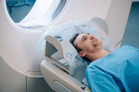 Hombre guapo adulto acostado en la cama de tomografía computarizada durante la prueba de tomografía