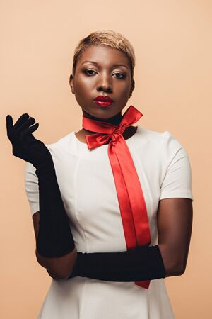 Young African American woman posing in white dress, red scarf and black gloves isolated on beige background