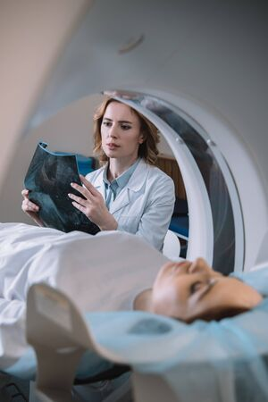 Selective focus of thoughtful radiologist holding x-ray diagnosis during patients diagnostics