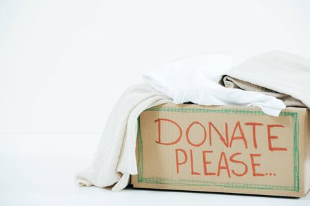 Cardboard box with inscription and donated clothes on white background Reklamní fotografie