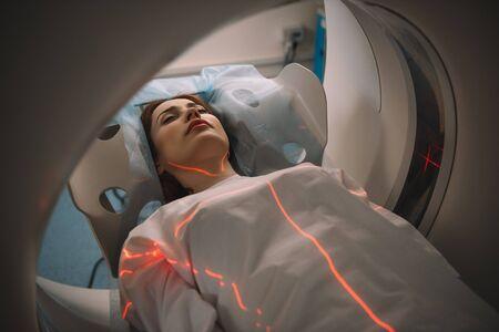 Schöne Frau, die während des Tomographietests im Krankenhaus auf dem CT-Scannerbett liegt