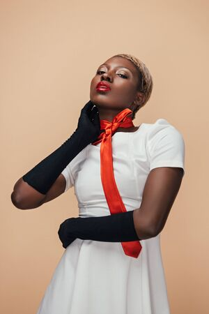 Sexy African American girl posing in white dress, red scarf and black gloves isolated on beige background