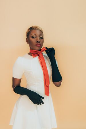 Stylish African American girl posing in trendy red scarf and black gloves isolated on beige background