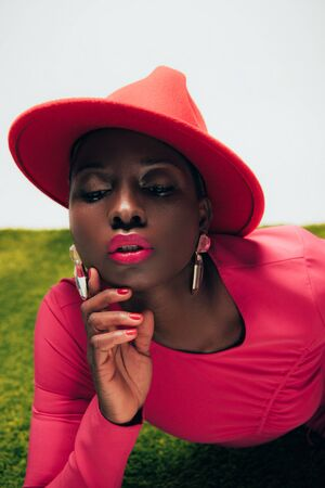 Beautiful stylish African American woman in pink dress and hat posing on green grass background Stock Photo