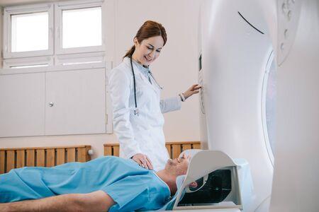 Pretty young radiologist preparing man for tomography diagnostics in mri machine