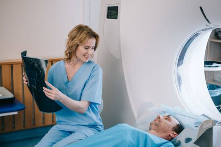 Beautiful smiling doctor holding radiology diagnosis and looking at man lying on ct scanner bed Zdjęcie Seryjne