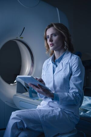 Thoughtful radiologist holding digital tablet with x-ray diagnosis while sitting near computed tomography scanner and looking away Zdjęcie Seryjne