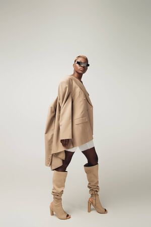 Stylish young African American girl posing in sunglasses and beige jacket on grey background
