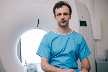 Thoughtful man sitting on ct scanner bed and looking at camera