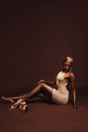Beautiful passionate African American model with short hair on brown background