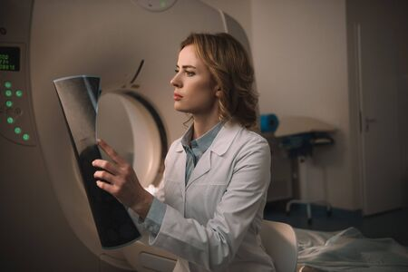 Thoughtful radiologist examining x-ray diagnosis while sitting near ct scanner