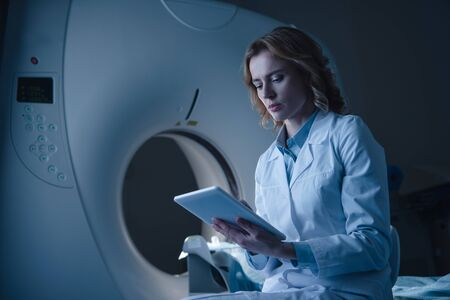 Serious doctor looking at digital tablet with x-ray diagnosis while sitting near ct scanner