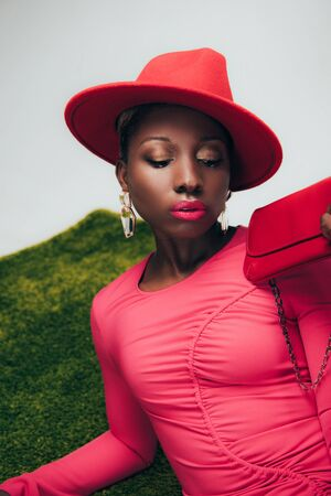 Attractive African American woman in pink dress and hat posing with bag on green grass background Stock Photo