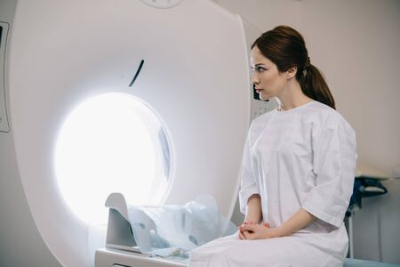 Attractive woman sitting on computed tomography scanner bed in hospital