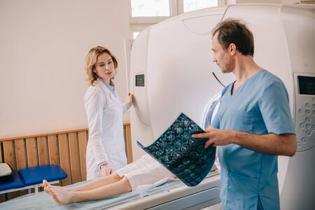 Doctor holding tomography diagnosis while radiologist operating ct scanner during patients diagnostics