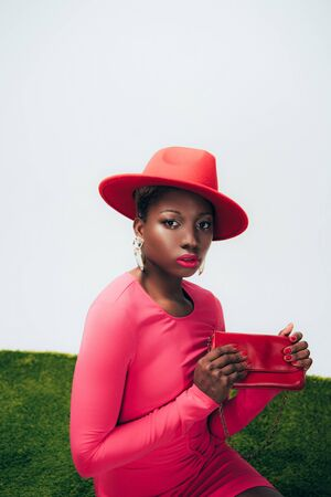 Elegant African American woman in pink dress and hat posing with bag on green grass background