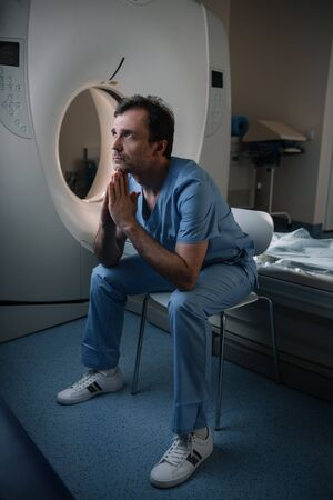 Serious doctor sitting near computed tomography scanner in hospital and looking up Zdjęcie Seryjne - 125221587