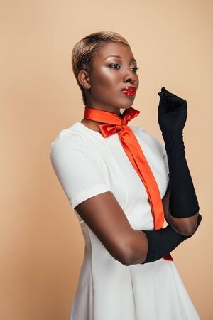Stylish African American girl posing in white dress, trendy scarf and black gloves isolated on beige background Stock Photo