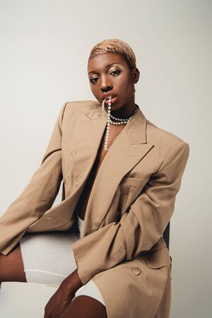 Fashionable African American woman in necklace and beige jacket sitting on chair isolated on grey background
