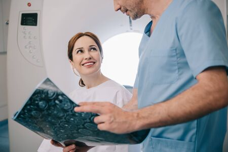 Cropped view of doctor showing x-ray diagnosis to happy woman