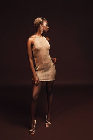Elegant African American woman with short hair posing in glamorous dress on brown background