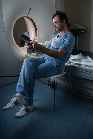 Thoughtful doctor examining x-ray diagnosis while sitting near computed tomography scanner