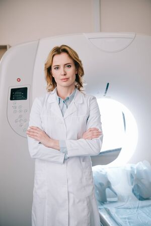 Beautiful radiologist standing near ct scanner with crossed arms and looking at camera