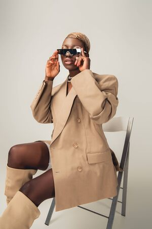 Fashionable African American model in sunglasses and beige jacket sitting on chair on grey background
