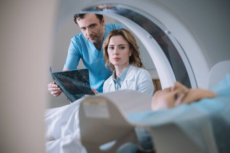 Selective focus of doctors holding x-ray diagnosis and looking at woman during diagnostics on computed tomography scanner