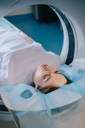 Pretty woman lying with closed eyes on ct scanner bed during diagnostics