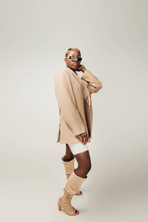 Fashionable African American girl posing in sunglasses and beige jacket on grey background