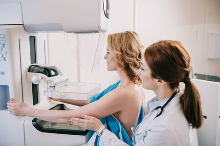 Young radiographer standing near patient while making mammography test on x-ray machine Stock Photo