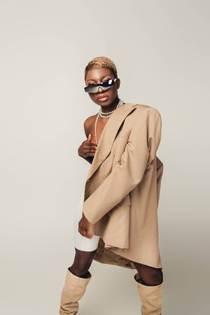 Naked African American girl posing in beige jacket isolated on grey background