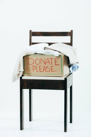 Cardboard box with donated clothes on wooden chair on white background Reklamní fotografie