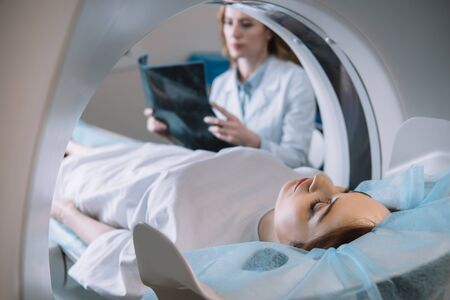 Selective focus of radiologist holding x-ray diagnosis while patient lying on ct scanner bed during diagnostics