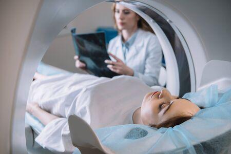 Selektiver Fokus des Radiologen, der eine Röntgendiagnose hält, während der Patient während der Diagnose auf dem CT-Scannerbett liegt
