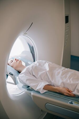 Woman with closed eyes lying on computed tomography scanner table during radiology test