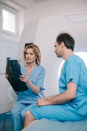 Beautiful doctor looking at x-ray diagnosis near patient sitting on mri scanner bed