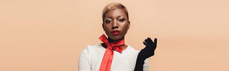 Fashionable attractive African American girl posing in red scarf and black gloves isolated on beige background Stock Photo