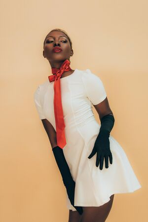 Sensual African American girl posing in white dress, red scarf and black gloves isolated on beige background Stock Photo