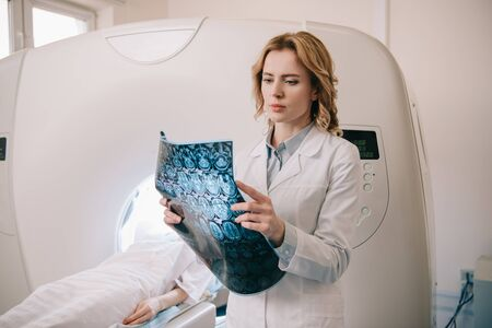 Thoughtful radiologist examining tomography diagnosis during patients diagnostics