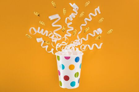 white and golden ribbons in polka dot cup on orange background