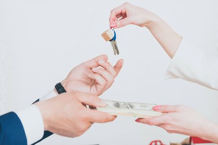 cropped view of client holding keys while giving dollar banknotes to realtor Stock Photo