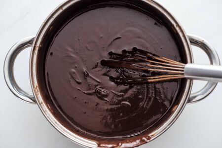 Top view of pan with melted dark chocolate and balloon whisk