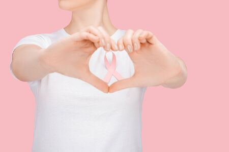 partial view of woman in white t-shirt doing heart sign with hands around pink breast cancer ribbon isolated on pink
