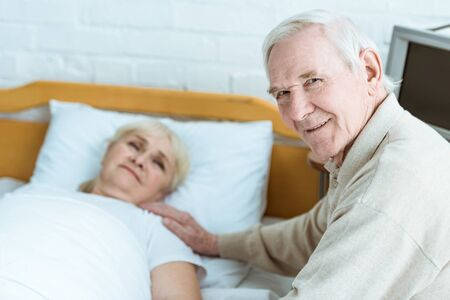 smiling senior man with sick wife in clinic Stock Photo