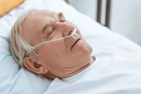 senior unconscious patient with nasal cannula in hospital