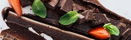 Panoramic shot of pieces of chocolate with fresh mint and strawberries