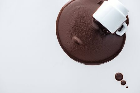 Top view of cup with spilling chocolate and chocolate drops on white background